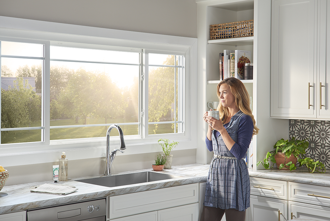 woman standing in her kitchen looking out her window