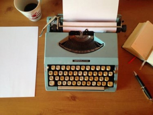 blue typewriter with blank sheet of paper