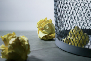 balled up pieces of yellow paper next to a trash can on the floor