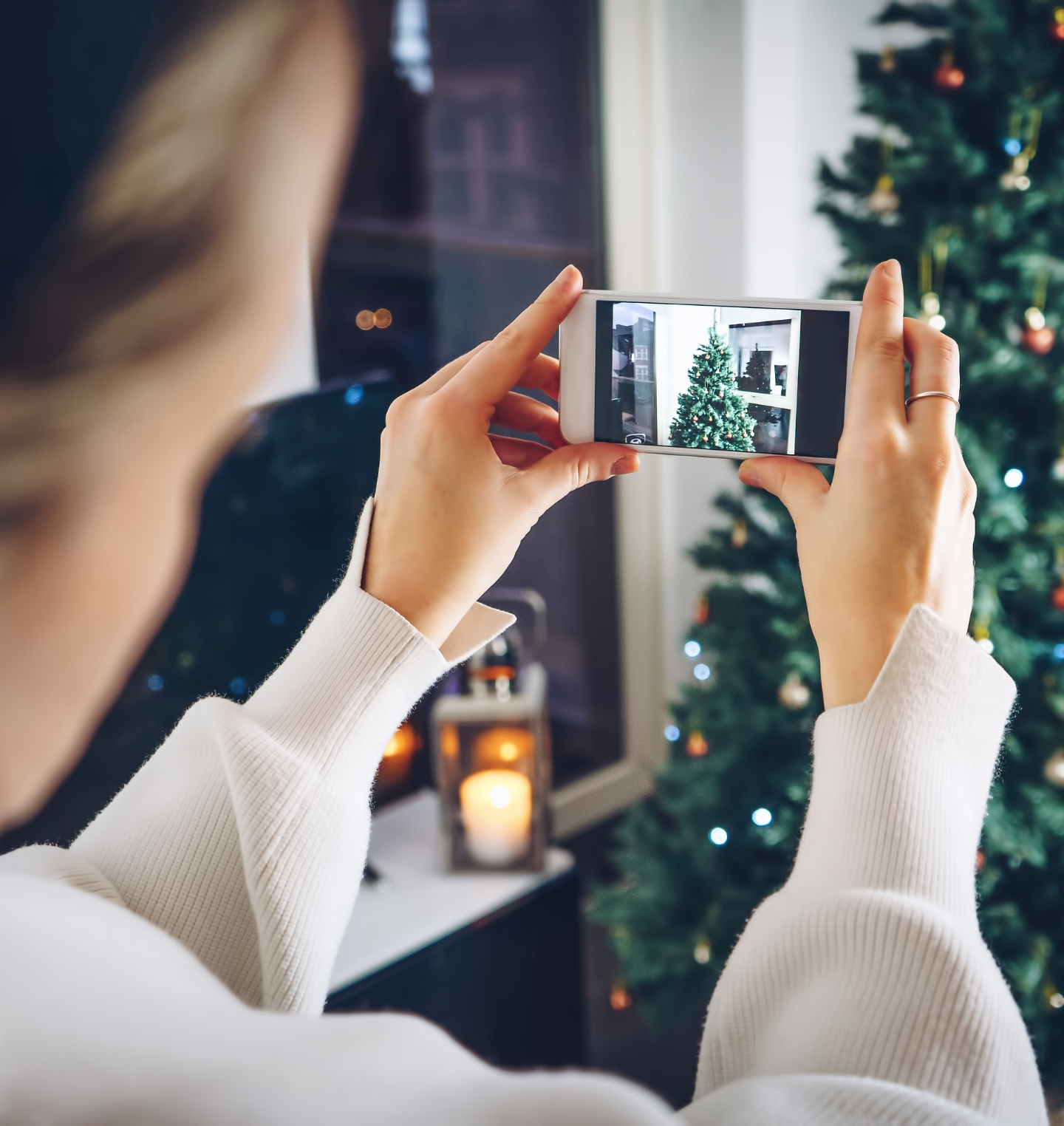 woman taking a picture of a christmas tree on her cell phone