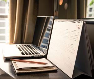 computer, notebook, and calendar on a desk